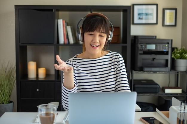Het aziatische vrouwenwerk thuis met de computer. luisteren online les. audioprogramma met hoofdtelefoon.