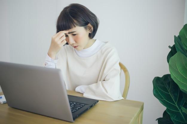 Het aziatische vrouwenwerk vanuit huis. ze is serieus en stress.