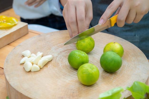 Het aziatische wijfje houdt oranje mes om groene citroenkalk op de houten cirkelplaat met garlice ernaast te schuiven.