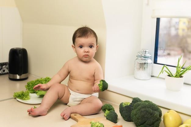 Het babymeisje houdt broccoli