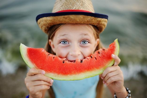 Het babymeisje in de hoed eet enthousiast aan sappige watermeloen op overzeese achtergrond