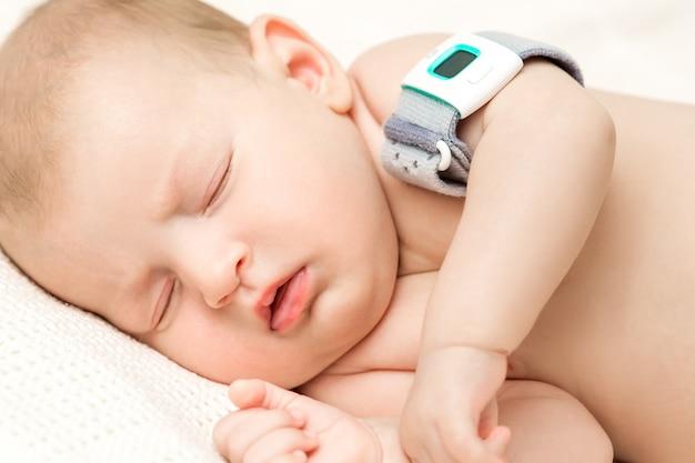 Het babymeisje in de voederbak meet lichaamstemperatuur
