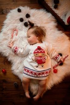Het babymeisje in een rood kerstmiskostuum met retro slingers zit op een bont