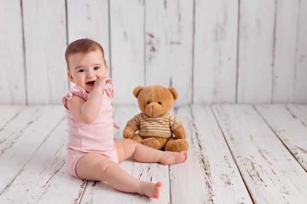 Het babymeisje in een roze bodysuit zit met een teddybeer