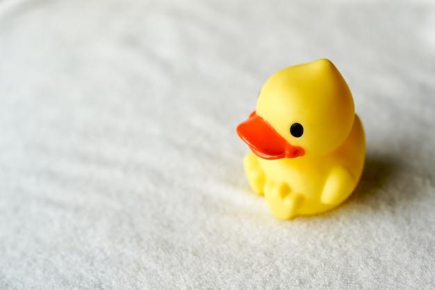 Het badstuk speelgoed van de baby gele eend op witte handdoek, exemplaarruimte