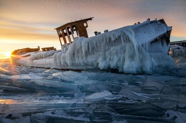 Het baikalmeer bij zonsondergang, alles is bedekt met ijs en sneeuw, dik helderblauw ijs. het baikalmeer in de stralen van de ondergaande zon. geweldige plek, unesco werelderfgoed
