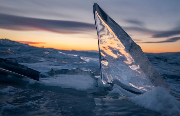 Het baikalmeer is bedekt met ijs en sneeuw, sterk koud, dik helderblauw ijs