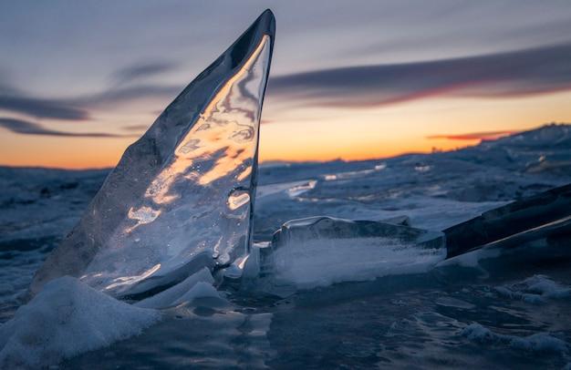 Het baikalmeer is bedekt met ijs en sneeuw, sterke kou, dik helderblauw ijs. aan de rotsen hangen ijspegels. het baikalmeer is een ijzige winterdag. geweldige plek, erfgoed, schoonheid van rusland?