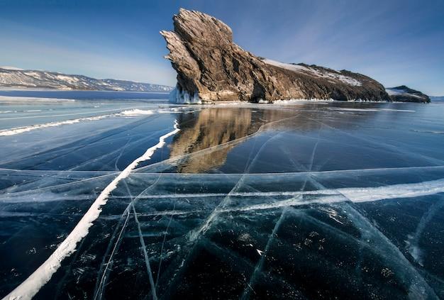Het baikalmeer is bedekt met ijs en sneeuw, sterke kou en vorst, dik helderblauw ijs. ijspegels hangen aan de rotsen. geweldige plek erfgoed