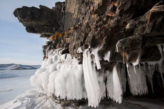 Het baikalmeer is een ijzige winterdag. grootste zoetwatermeer. het baikalmeer is bedekt met ijs en sneeuw, sterke kou en vorst, dik helderblauw ijs. aan de rotsen hangen ijspegels. geweldige plek erfgoed