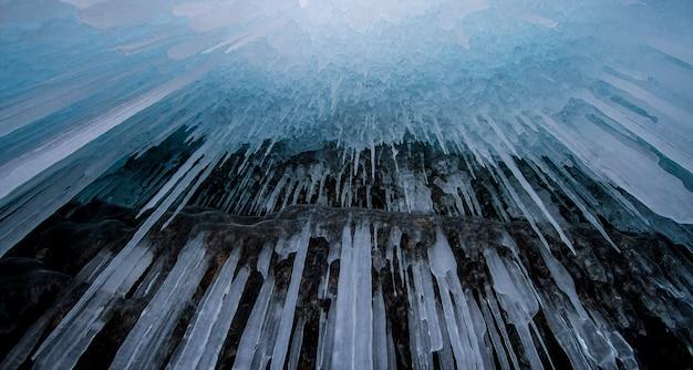 Het baikalmeer is een ijzige winterdag. grootste zoetwatermeer. het baikalmeer is bedekt met ijs en sneeuw, sterke kou en vorst, dik helderblauw ijs. ijspegels hangen aan de rotsen. geweldige plek erfgoed
