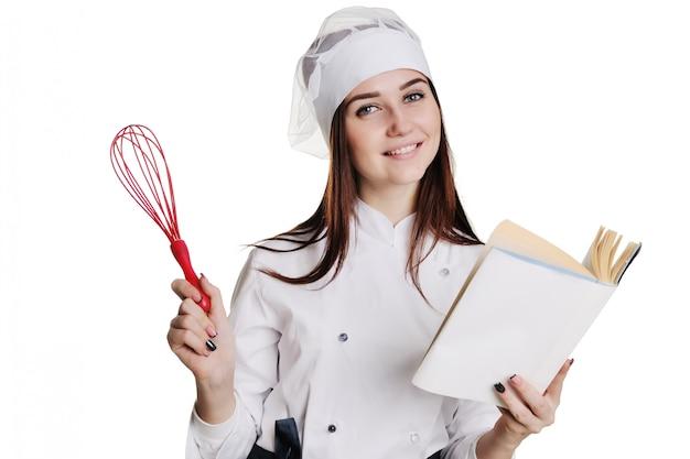 Het baker meisje met zwaait en kookt boek dat op witte achtergrond wordt geïsoleerd