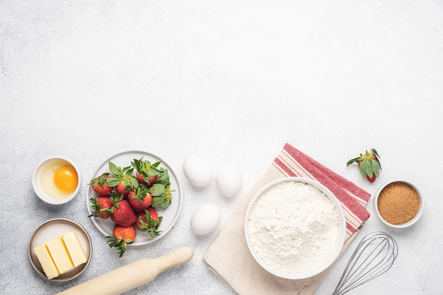 Het bakken van aardbeientaart witte achtergrond. meel, boter, eieren en keukengerei op witte stenen tafel
