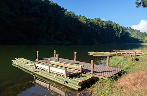 Het bamboevlot drijft bij de houten pier voor de toeristen