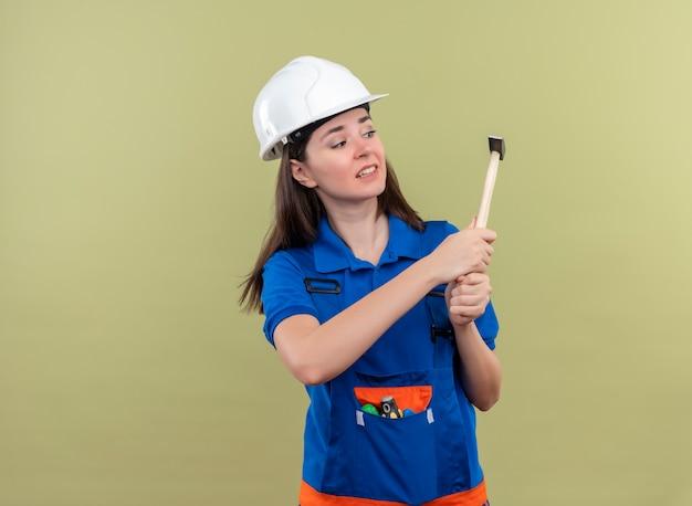 Het bang jonge bouwersmeisje met witte veiligheidshelm en blauw uniform houdt hamer met beide handen op geïsoleerde groene achtergrond