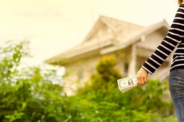 Het bankbiljet in vrouwenhand ziet uit op een huis