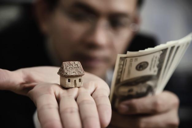 Het bankbiljet van het bedrijfsmensen toont geld maakt het financiële plan mensen uitnodigen om huis en auto te verkopen of te kopen - het monetaire kredietconcept van de leenkredietverzekering