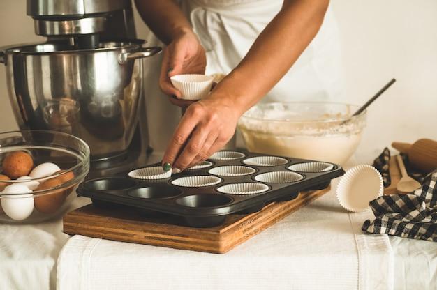 Het banketbakkersmeisje bereidt cupcakes voor. conceptingrediënten voor het koken van bloemproducten of dessert. landelijke of rustieke stijl.
