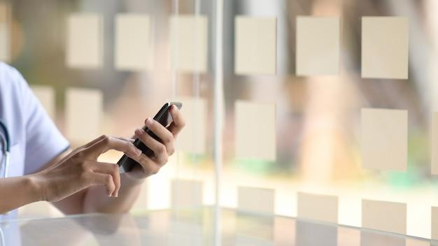 Het bebouwde beeld van arts die mobiele telefoon met behulp van dient binnen bureau in