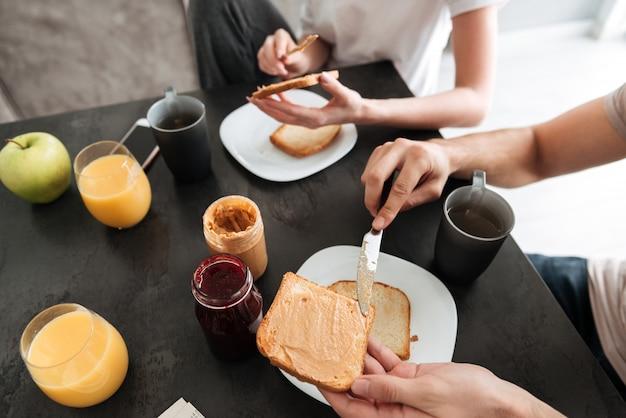 Het bebouwde beeld van paar heeft smakelijk ontbijt in de keuken