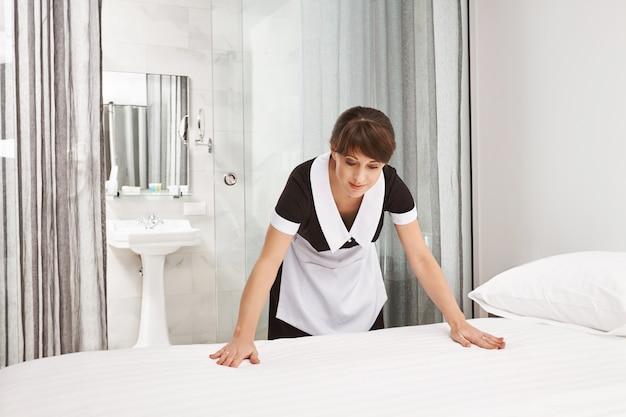Het bedoppervlak moet schoon en netjes zijn. binnenschot van vrouw die eenvormig meisje dragen, bed maken en glimlachen, in goede stemming zijn terwijl het werken in hotel als dienstmeisje. werknemer schoonmaakruimte van haar werkgever