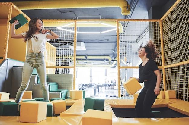 Het bedrijf is een jonge vrouw die zich vermaakt met zachte blokken op een kinderspeeltuin in een trampolinecentrum.