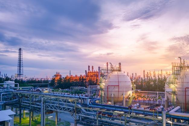 Het bedrijf van de olieraffinaderij met zonsondergang