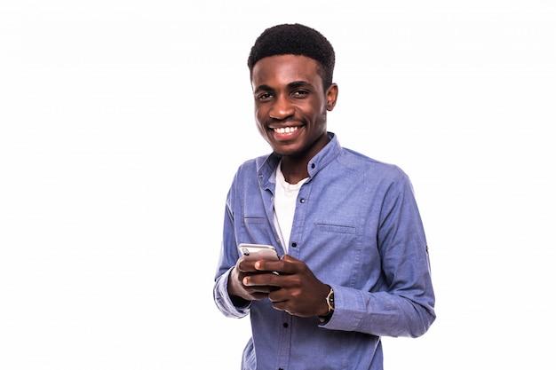 Het bedrijfs mens texting op zijn mobiele telefoon die over een witte muur wordt geïsoleerd