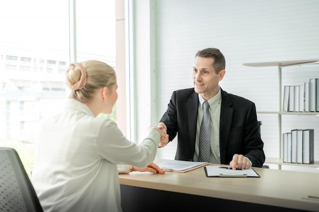 Het bedrijfsman en vrouwen schudden handen op bureau na baangesprek in vergaderzaal op kantoor