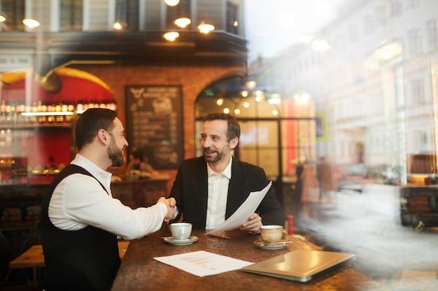 Het bedrijfsmensen schudden dient restaurant in Premium Foto