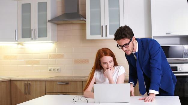 Het bedrijfspaar glimlachen die thuis met laptop in keuken werken