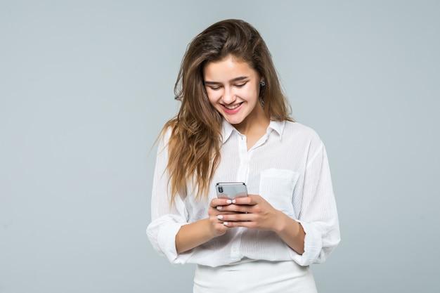 Het bedrijfsvrouw texting op haar mobiele telefoon - die over witte achtergrond wordt geïsoleerd