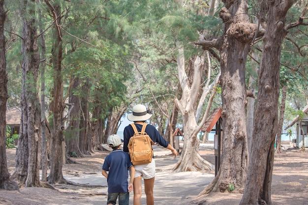 Het beeld achter moeder en zoon wandelen sandwalk weg met bomen bedekt achtergrond zee bij phraya nakhon cave national park, prachuap khiri khan, thailand.