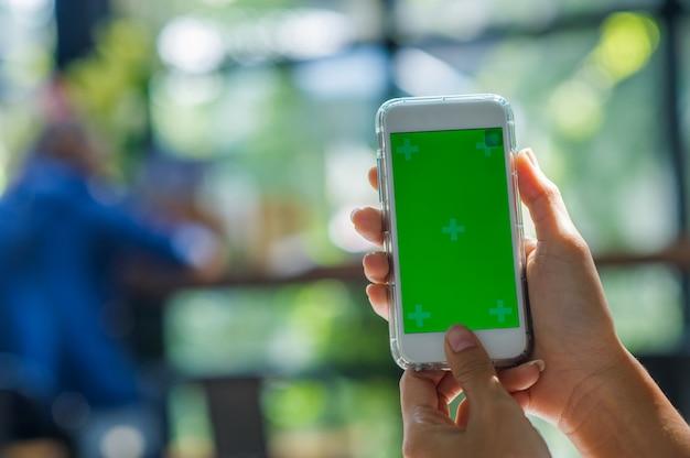 Het beeld is uit de hand van de vrouw gesneden met een smartphone met een leeg scherm voor tekst