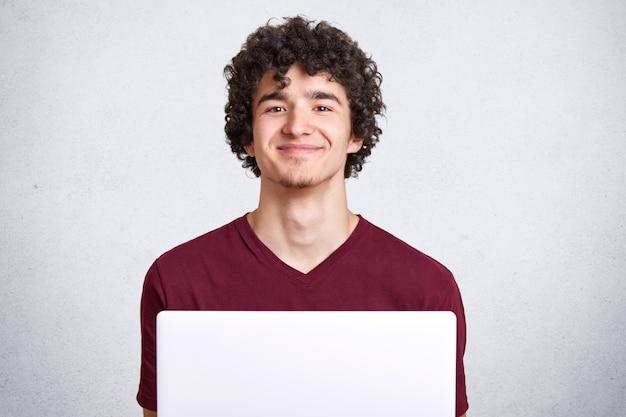 Het beeld van aantrekkelijke jonge kerel met krullend haar die toevallig kastanjebruin t-shirt dragen, voor open laptop zitten, direct glimlachend camera kijken, kijkt tevreden, geïsoleerd over witte studioachtergrond