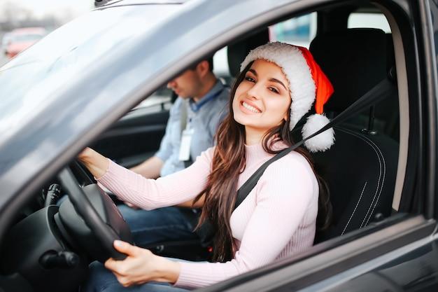 Het beeld van aantrekkelijke jonge vrouw zit op de plaats van de bestuurder