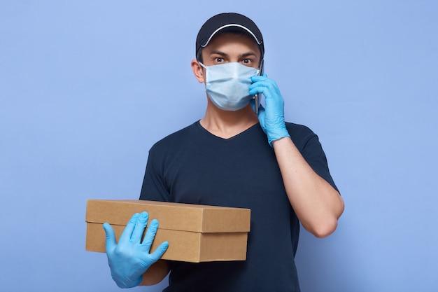 Het beeld van de bezorger die werknemer glb, t-shirt, masker en handschoenen dragen, houdt bruine kartondoos, kijkt verbaasd, spreekt telefonisch tegen blauwe muur.