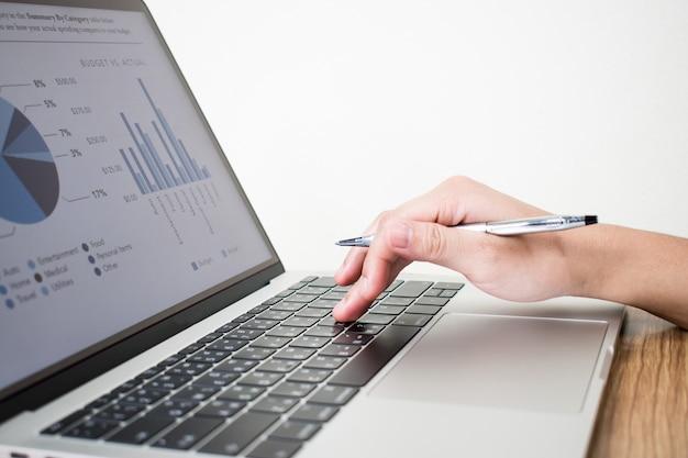 Het beeld van de hand van de zakenman die financiële grafiekgegevens op laptop creëren.