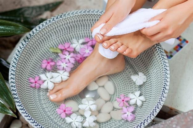 Het beeld van de ideale manicure en pedicure. vrouwelijke handen en benen in de spa-plek. massage