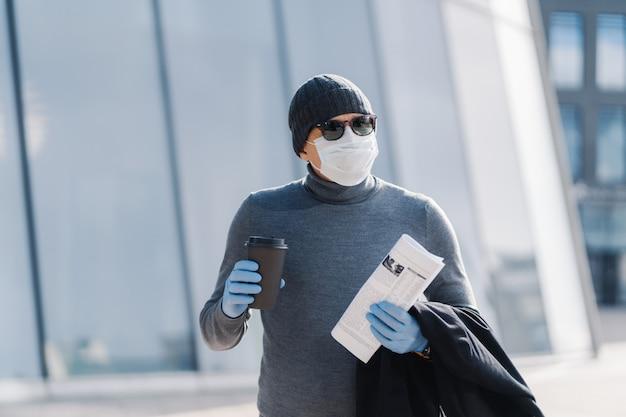 Het beeld van de jonge man draagt een steriel masker en rubberen medische handschoenen, kijkt opzij, loopt door de stad tijdens de verspreiding van besmettelijke ziekten, drinkt koffie, vouwt een krant. coronavirus preventieconcept
