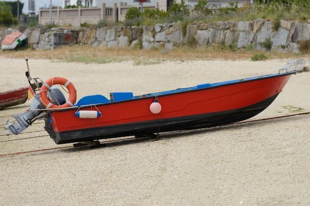 Het beeld van de rode houten vissersboot van de motorboot droogt aan wal