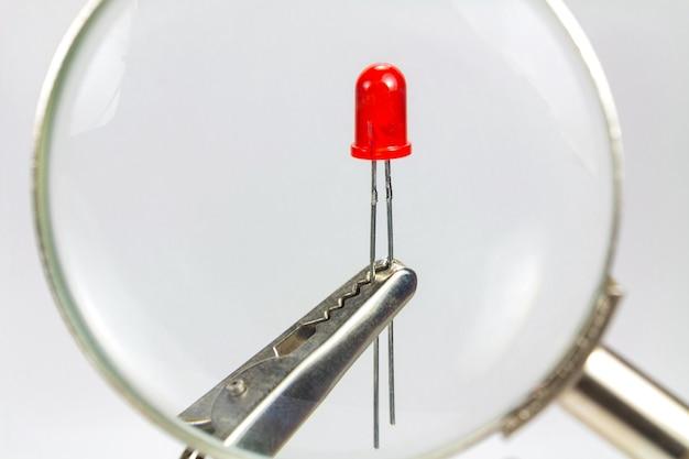 Het beeld van de rode led-diode door een vergrootglas