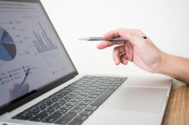 Het beeld van de zakenman analyseert de grafiek op laptop.