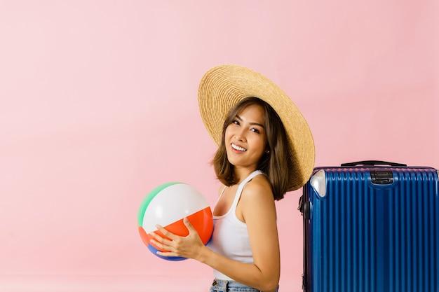 Het beeld van een aziatische vrouw met een hoed met een brede rand en staande zomerkleding met bagage