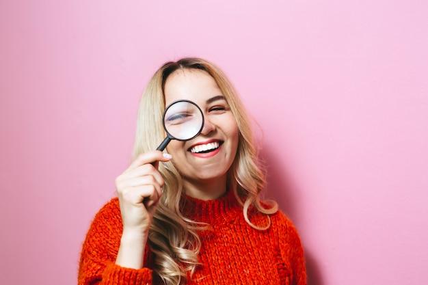 Het beeld van een blond meisje, gekleed in een rode trui en met een vergrootglas op een roze muur