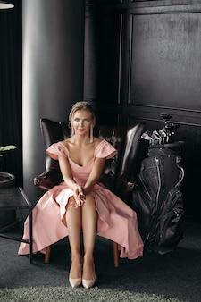 Het beeld van een charmante kaukasische dame zit op de zwarte leerleunstoel en stelt voor de camera