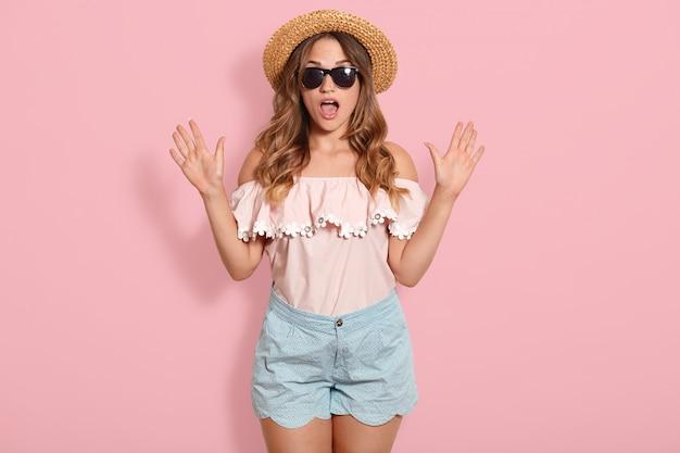 Het beeld van een jonge vrouw die een roze blouse, een blauwe korte broek, een zonnebril en een zomerstrohoed draagt met open mond in shock, houdt de handen omhoog, heeft een verbaasde gezichtsuitdrukking. menselijke emoties concept.