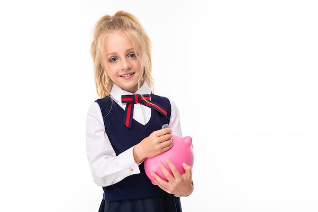 Het beeld van een klein meisje met blond haar houdt roze varkensspaarpot en glimlacht