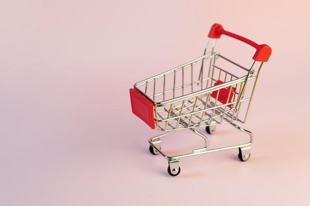 Het beeld van een leeg winkelwagentje of kar op roze achtergrond.