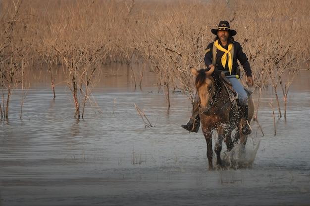 Het beeld van een man in een cowboyjurk en een paard dat over de rivier loopt